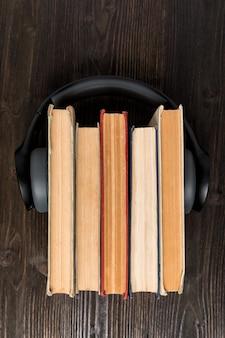 Несколько книг и наушников на деревянном фоне. слушайте концепцию аудиокниг. вертикальная рамка вид сверху.