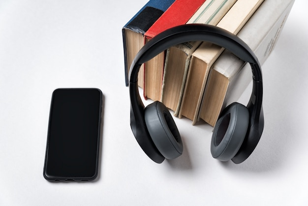 Few books, headphones and smartphone. modern learning with audio.
