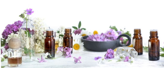 Few  bottles of essential oil among petals of flowers on a table
