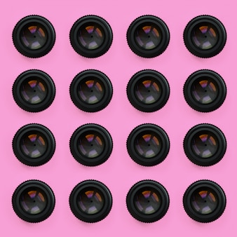 A few camera lenses with a closed aperture lie on pink texture