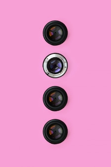 A few camera lenses with a closed aperture lie on texture background of fashion pastel pink color paper in minimal concept.