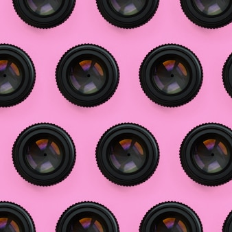 A few camera lenses with a closed aperture lie on texture background of fashion pastel pink