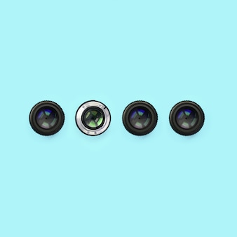 A few camera lenses with a closed aperture lie on texture of fashion pastel blue color paper