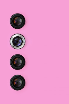 A few camera lenses with a closed aperture lie on texture