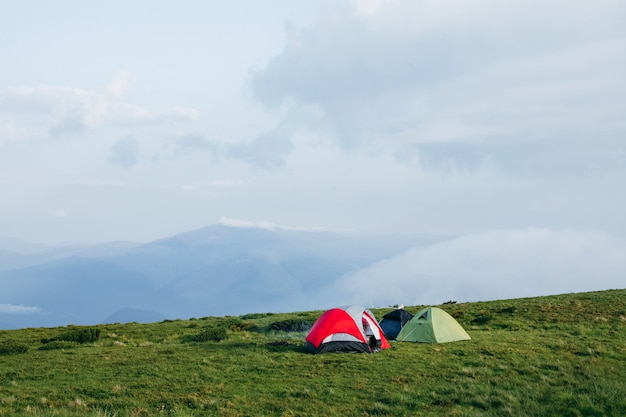 A few camping tents in the mountains on a foggy day