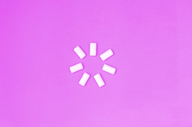 A few chewing gums lie on texture fashion pastel purple color paper