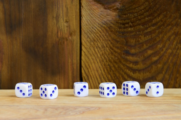 A few dice lies on the surface of natural wood.