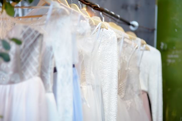 Few elegant wedding, bridesmaid ,evening, ball gown or prom dresses on a hanger in a bridal shop.