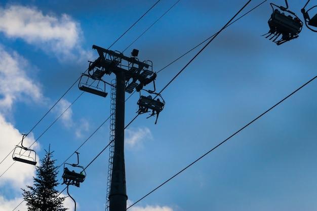 사람들과 아름다운 푸른 하늘이 있는 스키 리조트의 4인승 스키 스노우보드 리프트