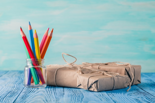 Несколько подарочных коробок и цветные карандаши в банке на столе
