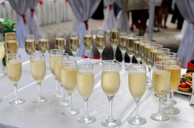 A few glasses of champagne arranged on a table in the shape of a heart