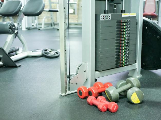 Few light weight dumbbells on a gym floor near heavy weight cross training machine