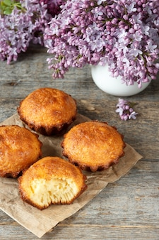 A few muffins on wooden background. a bouquet of lilacs, the broken cupcake. still life.