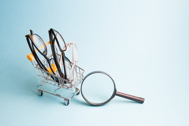 A few pairs of glasses in a small shopping cart, a magnifier on a light blue surface