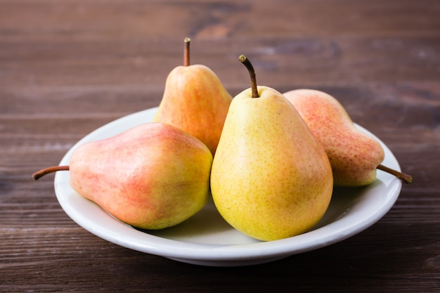 A few pears on a plate on a wooden table