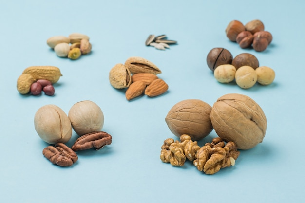 A few peeled and unpeeled nuts on a light blue surface