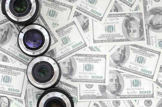 A few photographic lenses lies on the background of a lot of dollar bills.
