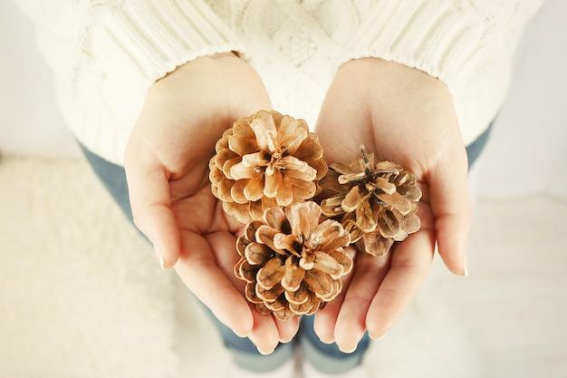 여자 손에 몇 소나무 콘, 근접 촬영