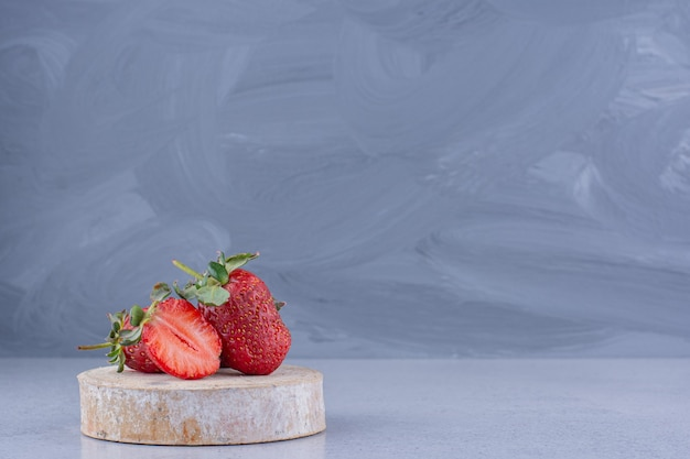 Few strawberries on a piece of wood on marble background.