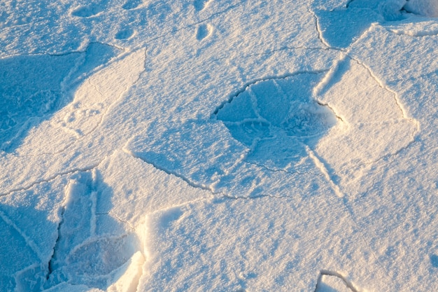 Few traces of men's shoes in the snow. on the snow there is shadow and cracks. photographed close-up.