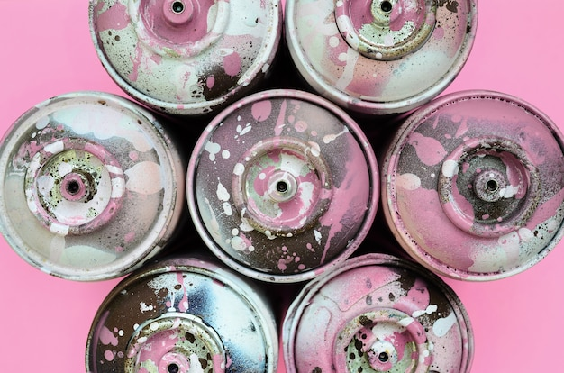A few used spray cans with pink paint drips lie on texture background
