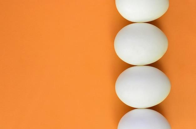 A few white easter eggs on a bright orange
