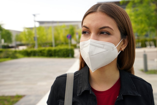 Ffp2保護マスク。予防と保護として通りで医療用フェイスマスクを着用している若い女性のクローズアップ。