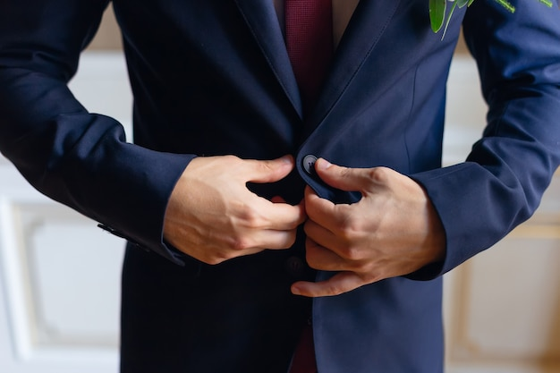 Fiance fasten the buttons on his blue jacket close up