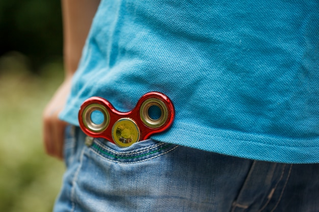 Fidget hand spinner in blue jeans pocket background. trendy and popular toy for children and adult.