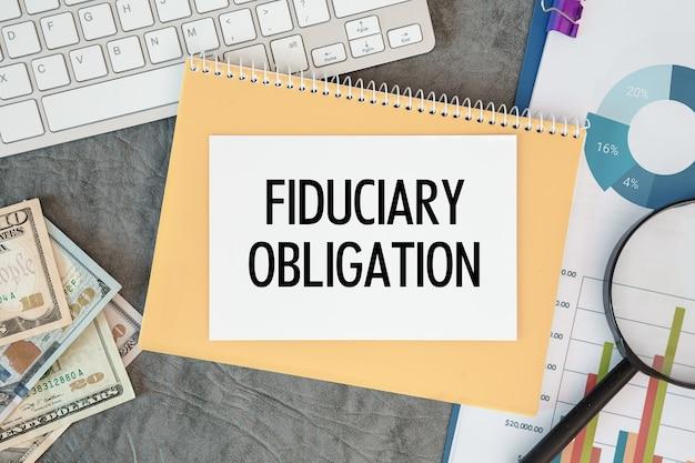 신탁 의무는 사무실 액세서리, 돈, 다이어그램 및 키보드와 함께 사무실 책상에 문서에 기록됩니다.