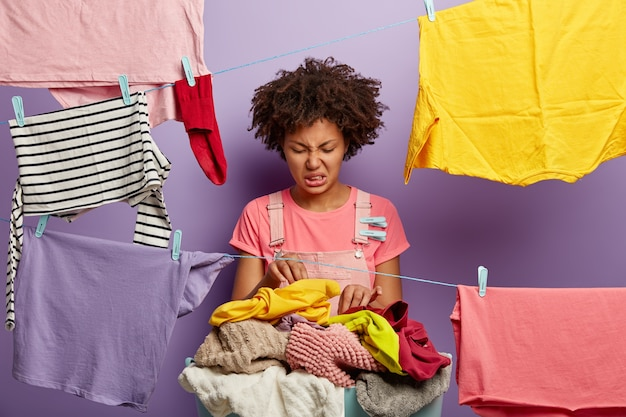 Fie, what dirty laundry! upset afro american female looks with dissatisfaction at pile of clothes for washing, frowns face from stench, poses near clotheslines, fed up of housework and cleaning