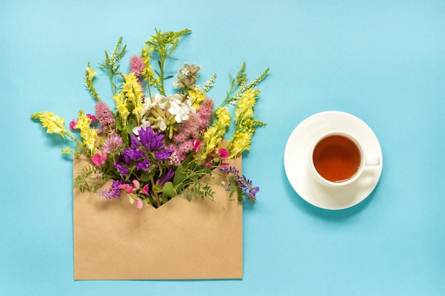 Field colorful flowers in craft envelope and cup of tea on blue