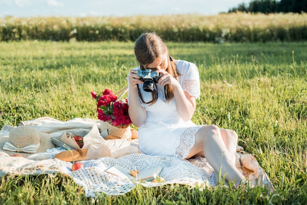 Field in daisies, a bouquet of flowers.french style romantic picnic setting. woman in cotton dress.takes pictures, photographer , strawberries, croissants, flowers on blanket. outdoor gathering.
