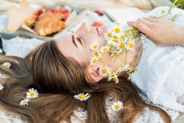 Field in daisies, a bouquet of flowers.summer picnic by the sea. basket for a picnic with with buns, apples and juice. girl on a picnic lies and reads a book