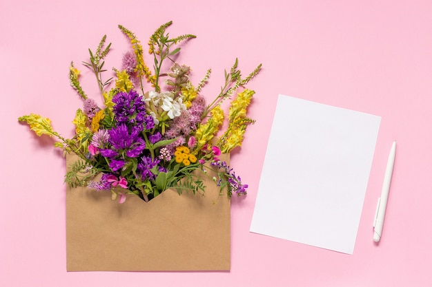 Field flowers in craft envelope and white empty paper card