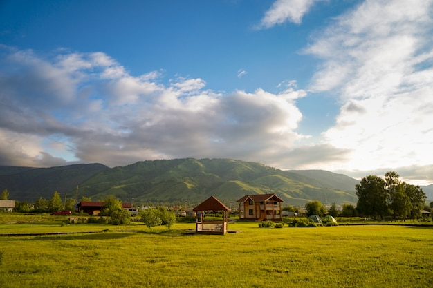 Field of green grass with small gazebo, cottage, touristic tents, and mountains