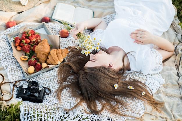 ヒナギクの畑、花の花束。夏の海でのピクニック。パン、リンゴ、ジュースが入ったピクニック用バスケット。ピクニックの女の子が嘘をついて本を読む