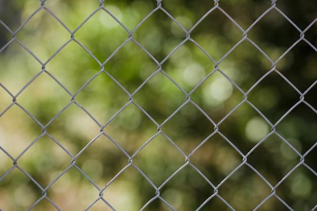 Поле стальной сетки забор, металлический забор из проволоки с травой на заднем плане.