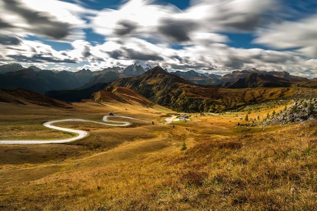 Поле в окружении скал, покрытых зеленью, под солнечным светом и облаками