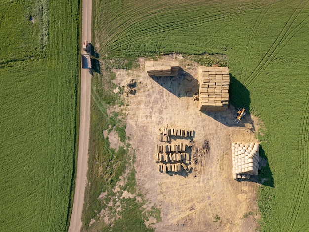 The field with bales of straw into the stack after harvesting the grain. top view. natural ecological fuel and fertilizers for agricultural work.