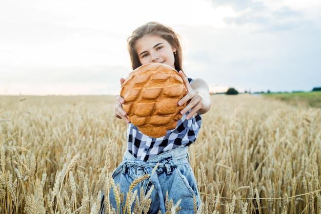 Поле с колосьями, урожай хлеба. девушка-подросток держит круглый хлеб. хлеб селективный фокус. руки держат большой хлеб. хлебобулочные изделия на пшеничном поле.
