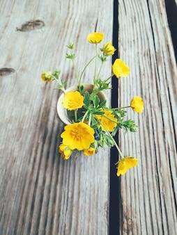 Field yellow flowers in blue vase
