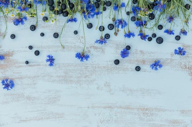 밝은 파란색 나무 테이블 위에 필드 꽃과 열매. 수레 국화, 카밀레 및 블루 베리와 테두리