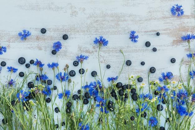 밝은 파란색 나무 테이블 위에 필드 꽃과 열매