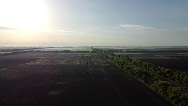 Поля ранним весенним летним утром с большой высоты. полет с высоты птичьего полета. шоссе и машины, которые по нему едут. сельское хозяйство, агрономия, земледелие, земледелие, руал, деревня. естественный фон