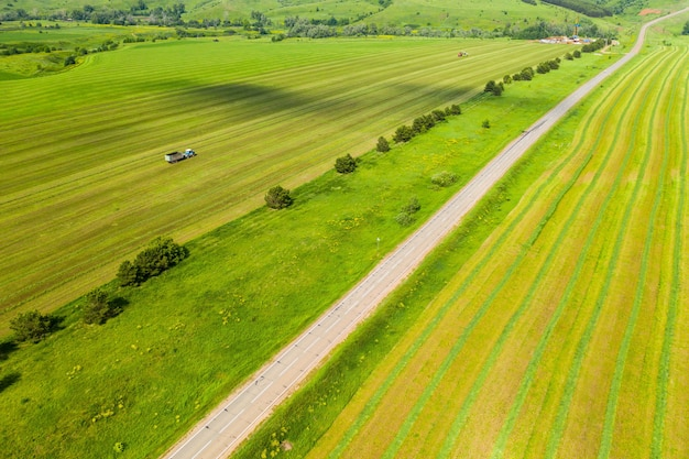 Fields and a road that goes into the distance taken by a drone
