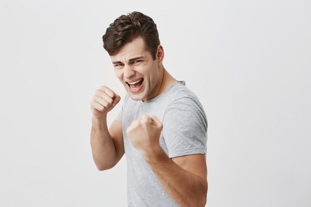 Maschio feroce e fiducioso con taglio di capelli alla moda che tiene i pugni davanti a sé come se fosse pronto per la lotta o qualsiasi sfida, dimostrando i suoi denti bianchi con rabbia, avendo un'espressione aggressiva sul viso