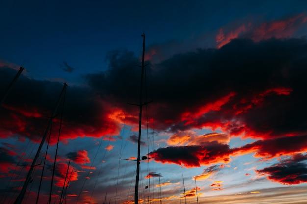 Огненные контрастные облака в голубом небе на закате сквозь мачты парусных яхт