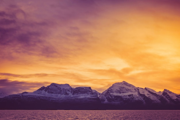 A fiery dawn over the snowy peaks of the fjord