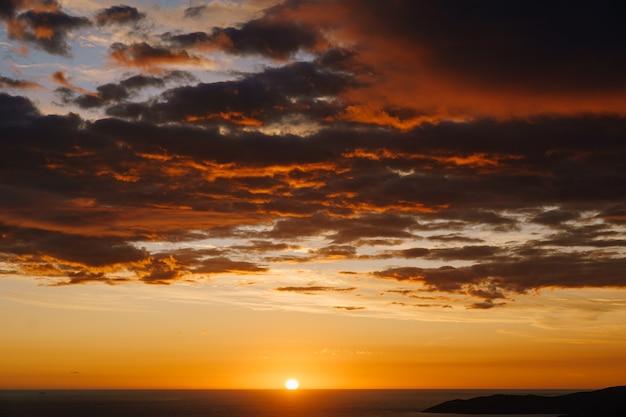 Огненно-оранжевый закат над морем солнце садится за горизонт оранжевые облака в небе